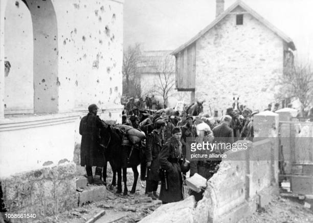 The Nazi propaganda picture shows soldiers of the German Wehrmacht taking a break from fighting partisans in a small village in Yugoslavia. The photo...