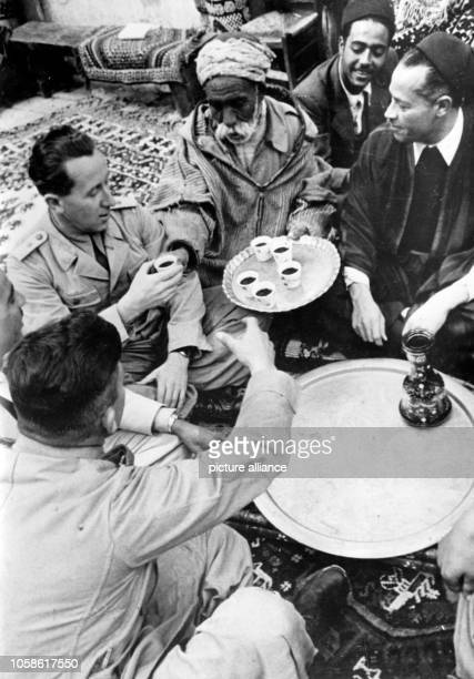 The Nazi propaganda picture shows Tunisian locals that reach a mocha coffee to soldiers of the German Wehrmacht The photo was taken in March 1943...