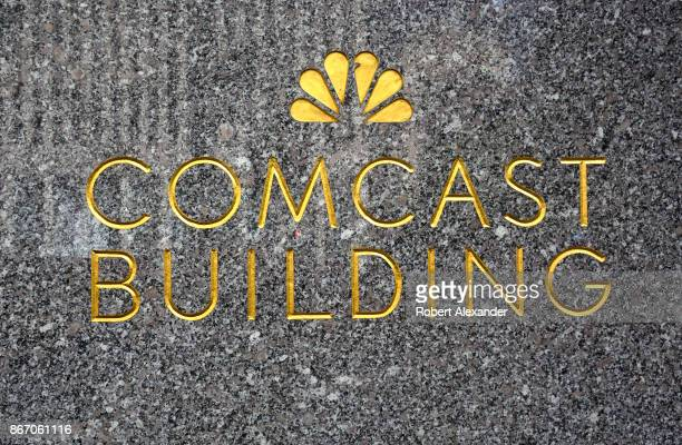 The NBCTV network peacock logo embellishes a granite wall near the entrance to the Comcast Building in New York New York The Comcast Corporation owns...
