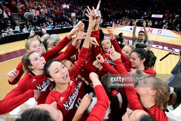 The Nebraska Cornhuskers celebrate their victory against the Illinois Fighting Illini during the Division I Women's Volleyball Semifinals held at the...