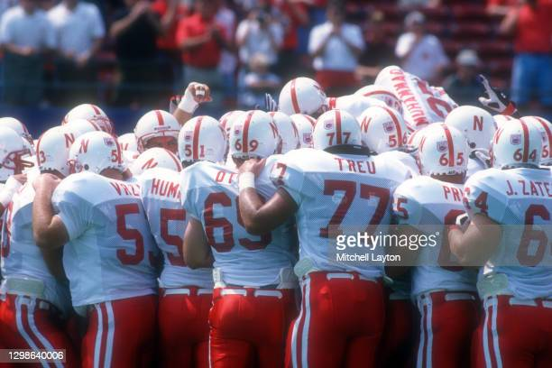 The Nebraska Cornhuskers huddle before a college football game against the West Virginia Mountaineers on August 31, 1994 at Giants Stadium in East...