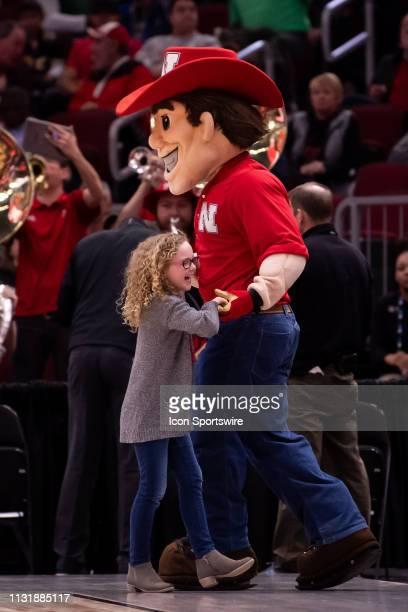 The Nebraska Cornhuskers mascot dances with a young fan during a Big Ten Tournament quarterfinal game between the Nebraska Cornhuskers and the...
