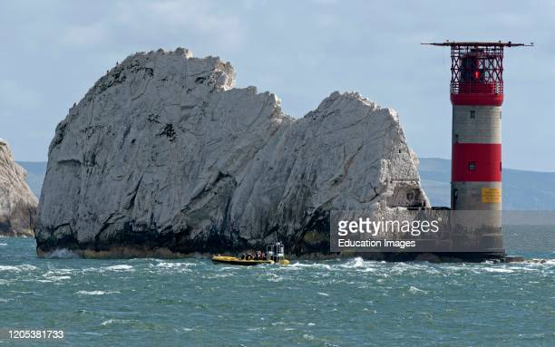 The Needles, Isle of Wight, England, UK, The Needles lighthouse with helipad situated on the outermost chalk rocks. Passengers on a rib viewing the...