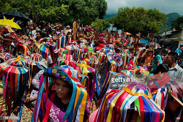 CONTENT] The Negritas dancers with colorful ribbons on hats walk in the religious procession in Atanquez Sierra Nevada Colombia A colorful...