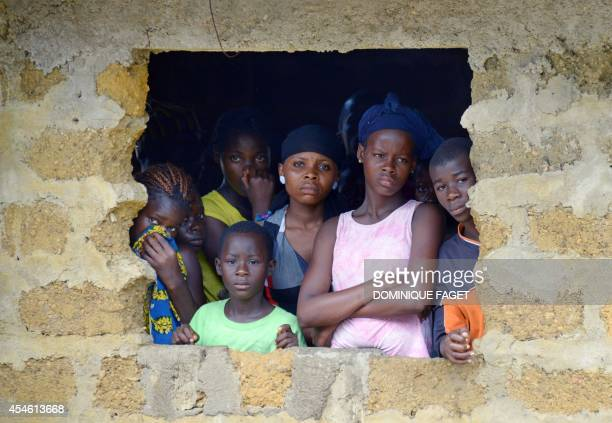 The neighbors of an Ebola virus victim look at medical workers of the Liberian Red Cross carry his body on September 4 2014 in the small city of...