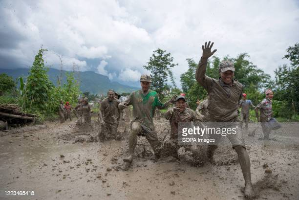The Nepalese farmers play in mud in the rice paddy field during the National paddy day. Nepalese farmers celebrate National Paddy Day which marks the...