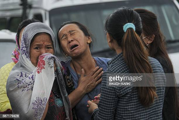 The Nepalese sister of Laxmi Gurung who was killed in a helicopter crash reacts as the bodies of victims are brought to a morgue of the Teaching...