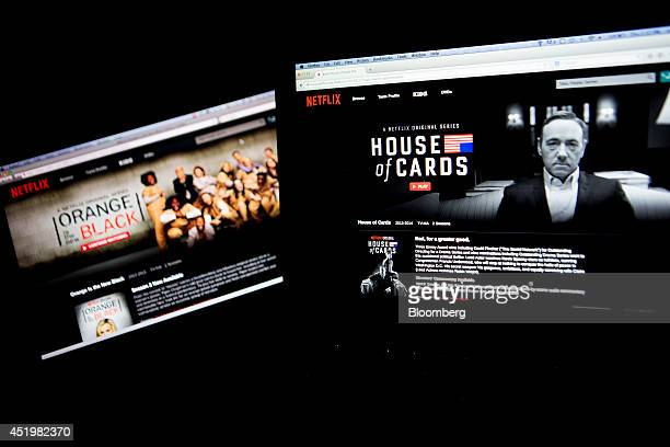 "The Netflix Inc. Website displays the ""Orange is the New Black"" and ""House of Cards"" series on laptop computers in this arranged photograph in..."