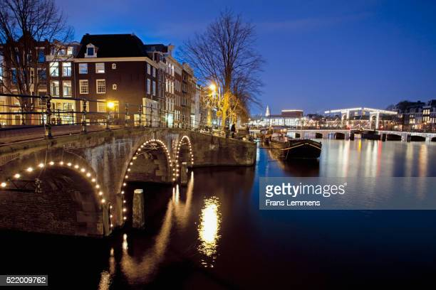 The Netherlands, Amsterdam, 17th century houses at river called Amstel. Unesco World Heritage Site. Background Skinny Bridge. Dusk.