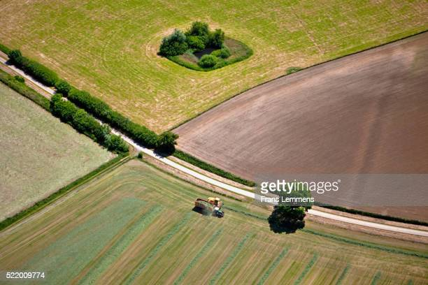 The Netherlands, Buren, Farmer working on grassland with tractor. Aerial