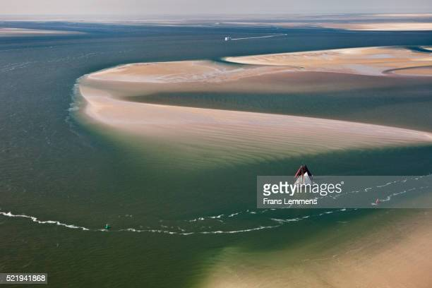 The Netherlands, Island Terschelling, Wadden Sea. Traditional cargo sailingships, tourist cruises. Unesco World Heritage Site. Aerial.