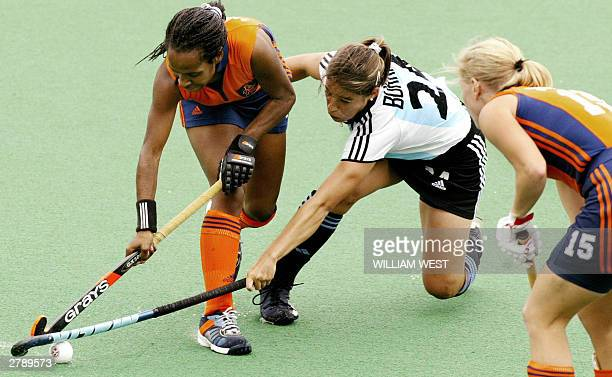 The Netherlands Maartje Scheepstra is tackled by Argentina's Caludia Burkart as Janneke Schopman also of the Netherlands looks on in their Womens'...