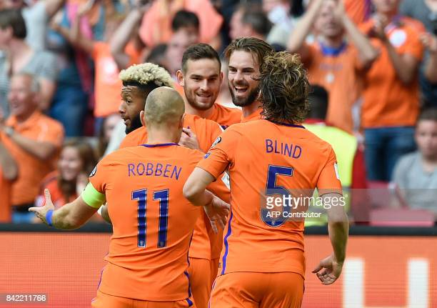 The Netherlands' midfielder Davy Propper celebrates with teammates after scoring a goal during the 2018 FIFA World Cup qualification football match...