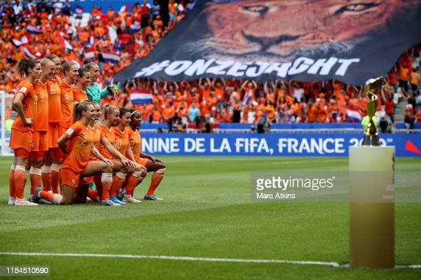 The Netherlands starting lineup pose for a photo in front of the World Cup trophy during the 2019 FIFA Women's World Cup France Final match between...