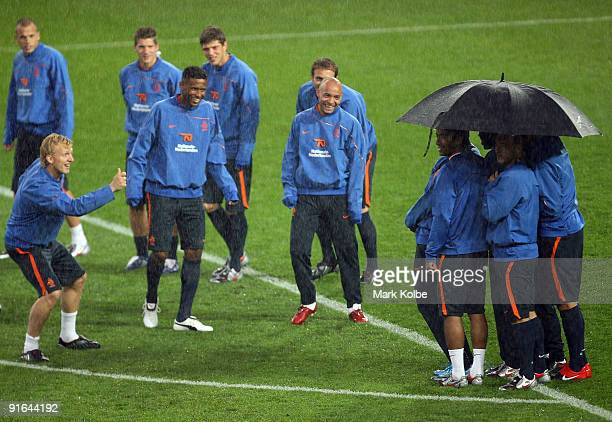 The Netherlands team share a joke as players huddle under an umbrella during the warmup in heavy rain during a Netherlands training session at Sydney...