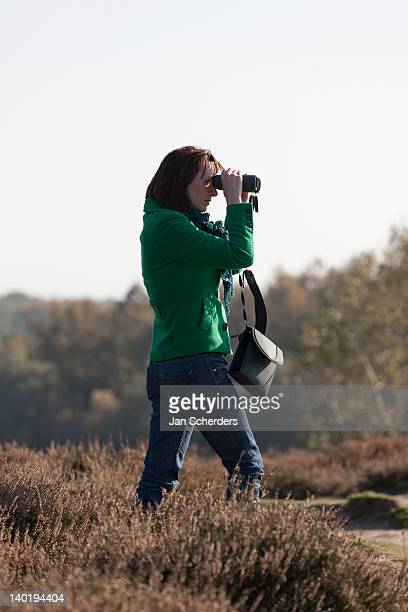 the netherlands, veluwezoom, posbank, woman in countryside looking through binoculars - posbank ストックフォトと画像