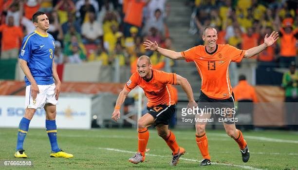 The Netherland's Wesley Sneijder celebrates with Andre Ooijer scoring his side's second goal of the game as Brazil's Lucio stands dejected