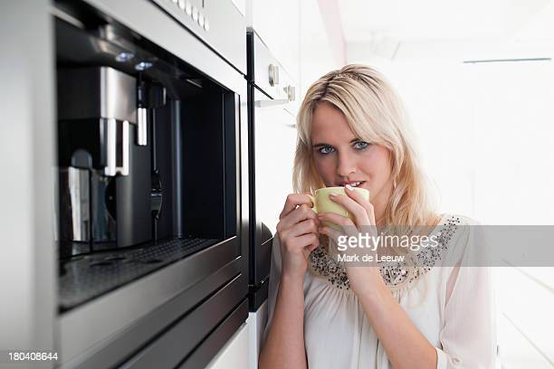 The Netherlands, Woman drinking coffee in kitchen