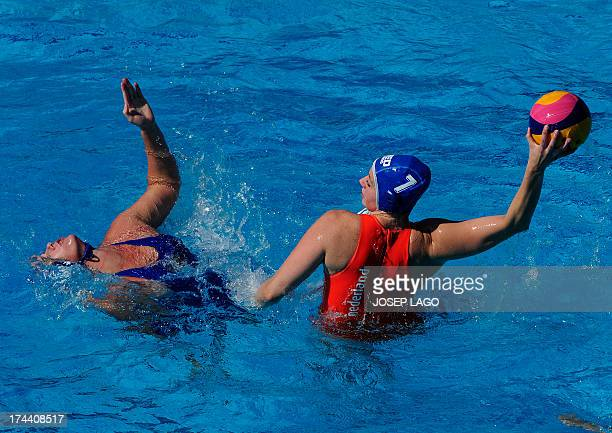 The Netherlands's Lefke van Belkum is held back by Russia's Olga Beliaeva during the preliminary rounds of the women's water polo event at the FINA...