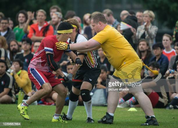The neutral player with the 'golden snitch' and a German player defend the snitch against a player from Norway in a match of the Quidditch World...