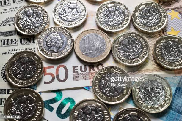 The new £1 pound coin is seen alongside US dollar bills and euro coins on April 4 2017 in Bath England Currency experts have warned that as the...