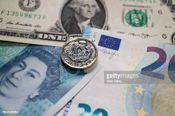 The new £1 pound coin is seen alongside US dollar bills and euro notes on April 4 2017 in Bath England Currency experts have warned that as the...