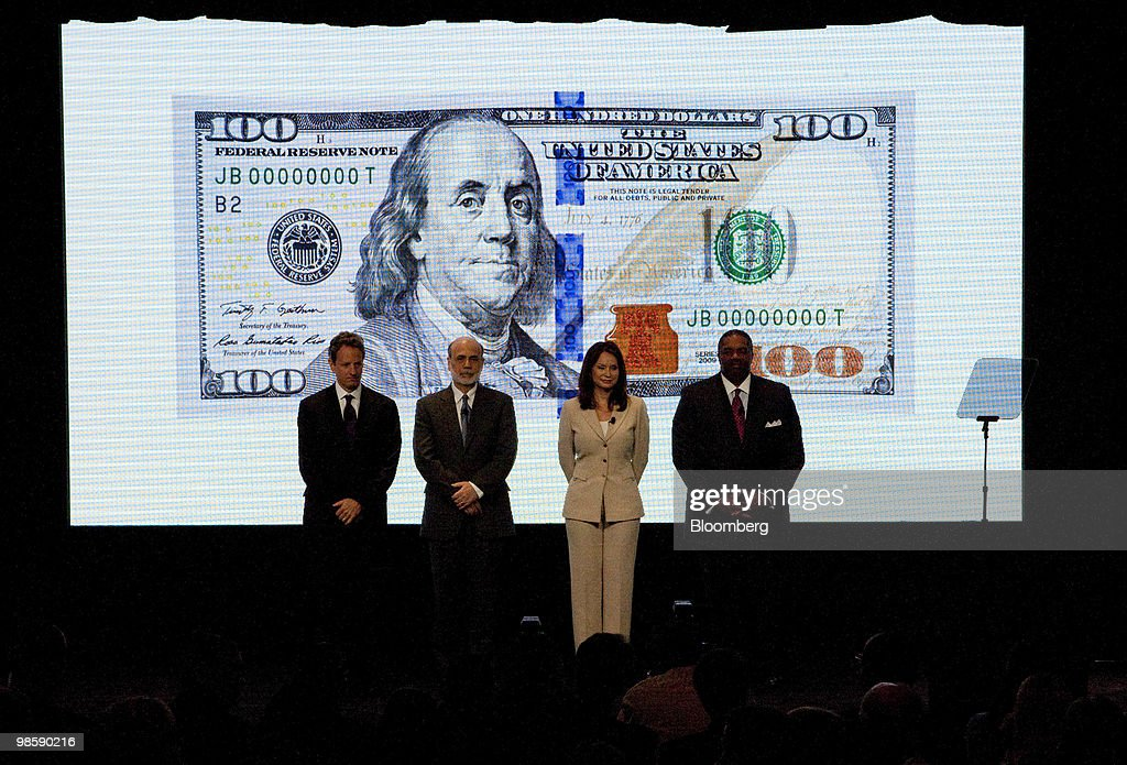 The new $100 bill is displayed on a screen behind Timothy Geithner, U.S. treasury secretary, left to right, Ben S. Bernanke, chairman of the U.S. Federal Reserve, Rosie Rios, U.S. treasurer, and Keith Prewitt, deputy director of the U.S. Secret Service, during its unveiling at the Treasury in Washington, D.C., U.S., on Wednesday, April 21, 2010. Complete with advanced technology to combat counterfeiting, the new design for the $100 note retains the traditional look of U.S. currency. Photographer: Andrew Harrer/Bloomberg via Getty Images