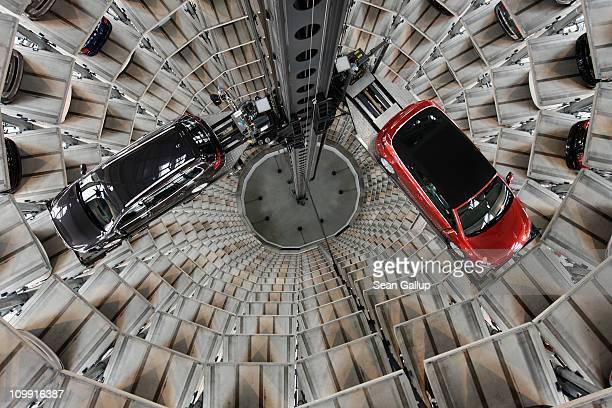 The new 2011 Volkswagen Passant Variant and new Golf Cabrio are lifted into one of two storage towers at the Autostadt customer reception center at...