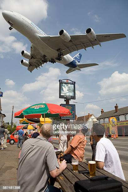 The new Airbus A380 double deck airliner seems to loom over patrons of The Swan pub as it comes in to land after a short display flight during the...