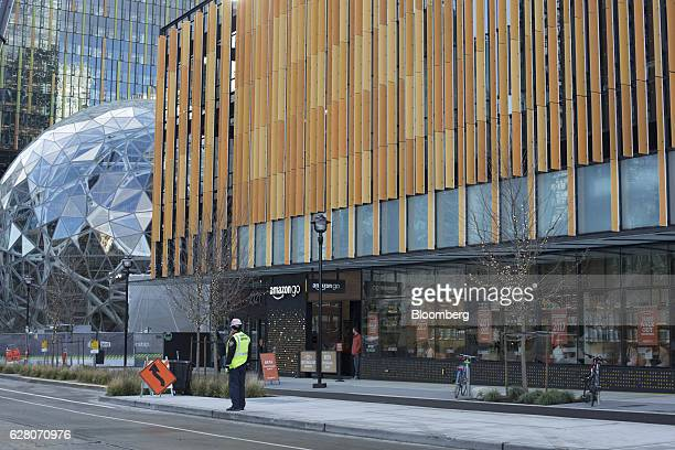The new Amazon Go grocery store stands next a glass dome sculpture part of the company's headquarters in Seattle Washington US on Tuesday Dec 6 2016...