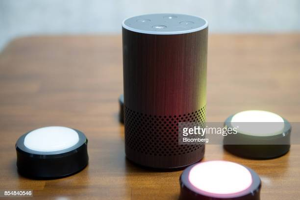 The new Amazoncom Inc Echo and Echo button devices sit on display during the company's product reveal launch event in downtown Seattle Washington US...
