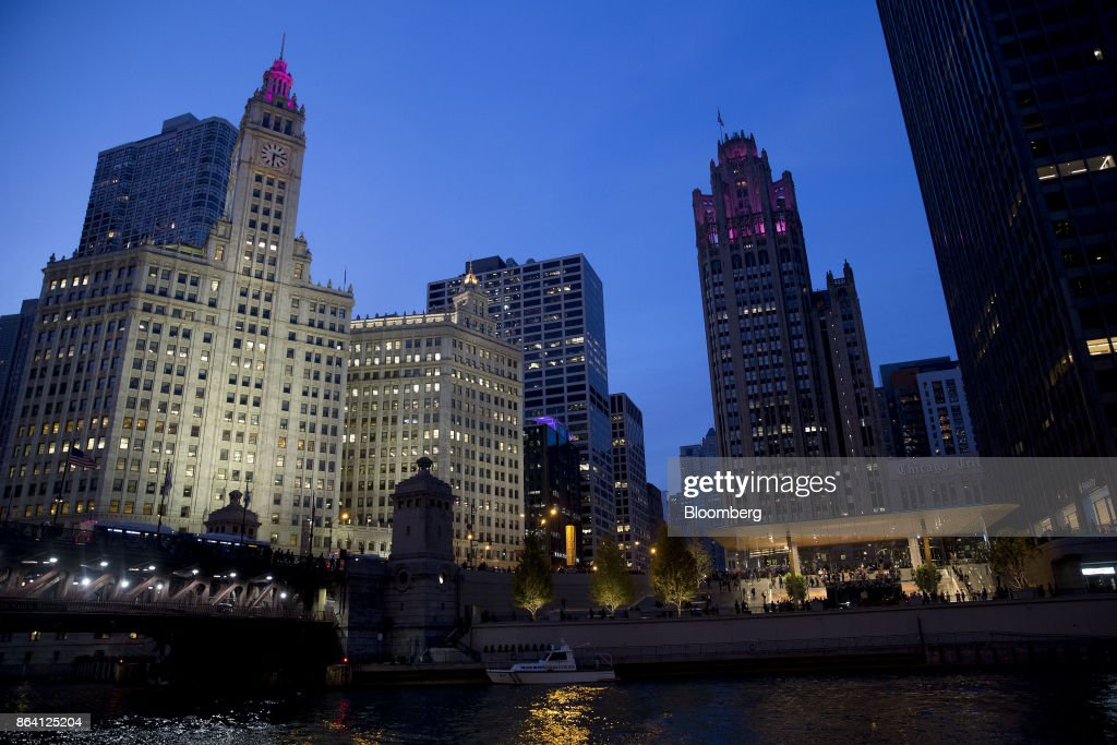 The new Apple Inc. Michigan Avenue store, lower right, stands illuminated on the banks of the Chicago River at dusk in Chicago, Illinois, U.S., on Friday, Oct. 20, 2017. The building features exterior walls made entirely of glass with four interior columns supporting a 111-by-98 foot carbon-fiber roof, designed to minimize the boundary between the city and the Chicago River. Photographer: Daniel Acker/Bloomberg via Getty Images