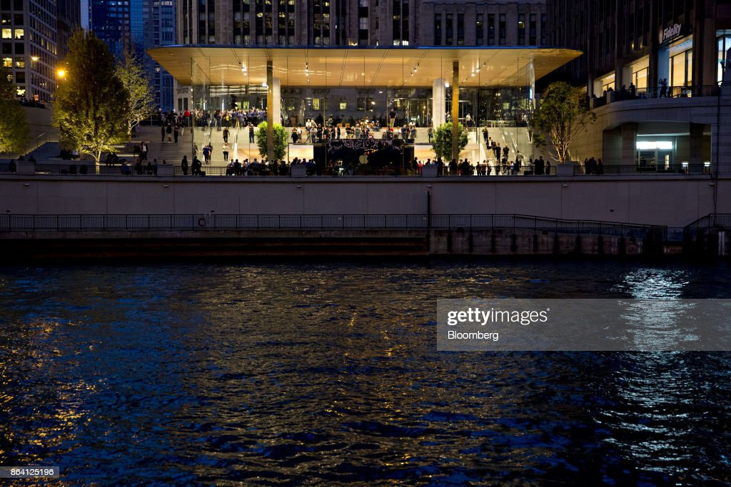 The new Apple Inc. Michigan Avenue store stands illuminated on the banks of the Chicago River at night in Chicago, Illinois, U.S., on Friday, Oct. 20, 2017. The building features exterior walls made entirely of glass with four interior columns supporting a 111-by-98 foot carbon-fiber roof, designed to minimize the boundary between the city and the Chicago River. Photographer: Daniel Acker/Bloomberg via Getty Images