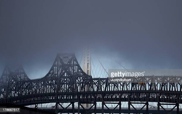 The new Bay Bridge SelfAnchored Suspension tower and the old eastern span of the bridge peek through fog on August 30 2013 in Oakland California...