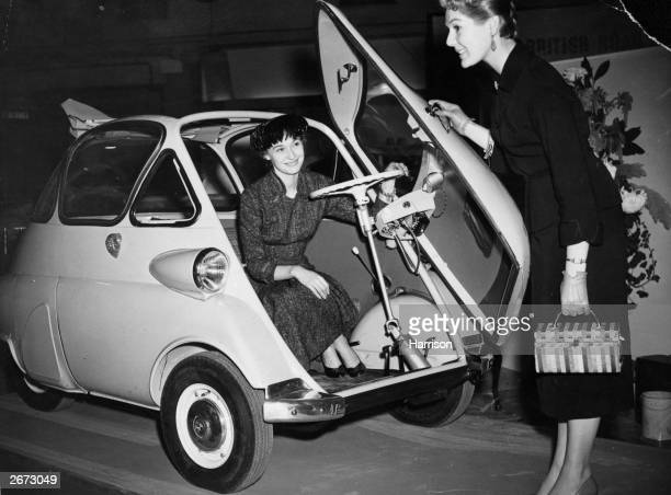 The new BMW Isetta a 250cc single cylinder aircooled fourwheeled car on show at the International Motor Show Earl's Court London The driver gets in...