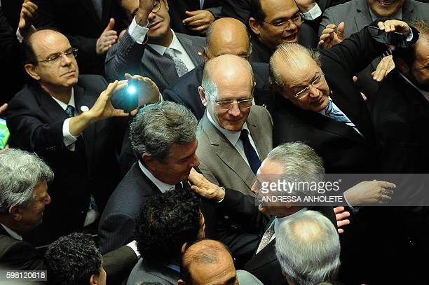 The new Brazilian President Michel Temer is greeted by Brazilian senator and former president Fernando Collor de Mello after taking office before the...