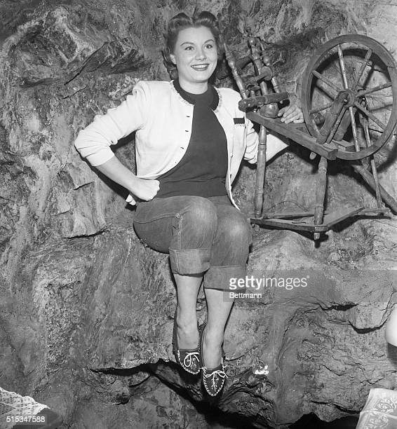 The new demure Barbara Payton poses by a spinning wheel on the set on her new movie in which the actress is starred in a naïvetype role Miss Payton...