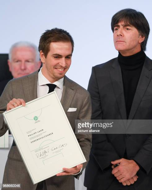The new DFB honourary team captain Philipp Lahm presents his document next to national soccer coach Joachim Loew at the extraordinary federal...