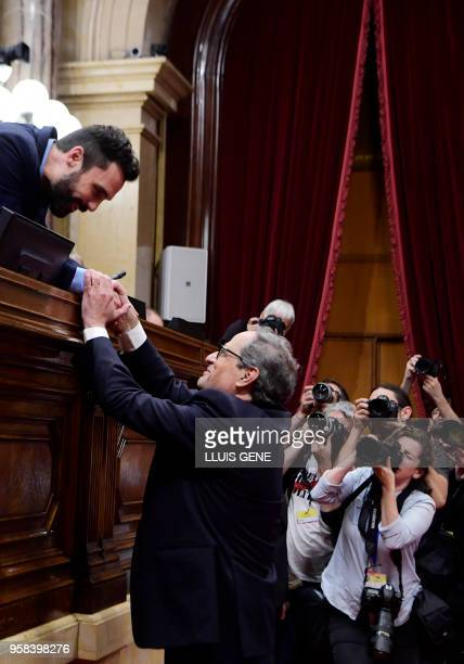The new elected Catalan regional president Quim Torra is congratulated by Catalan parliament's speaker Roger Torrent after a vote session at the...