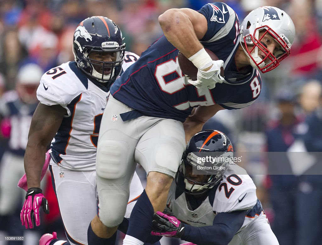 The New England Patriots' Rob Gronkowski is tackled by the Denver Broncos' Mike Adams with Joe Mays (#51) in pursuit after a 13-yard gain during second quarter action as the New England Patriots hosted the Denver Broncos in an NFL regular season game at Gillette Stadium on Sunday, Oct. 7, 2012.