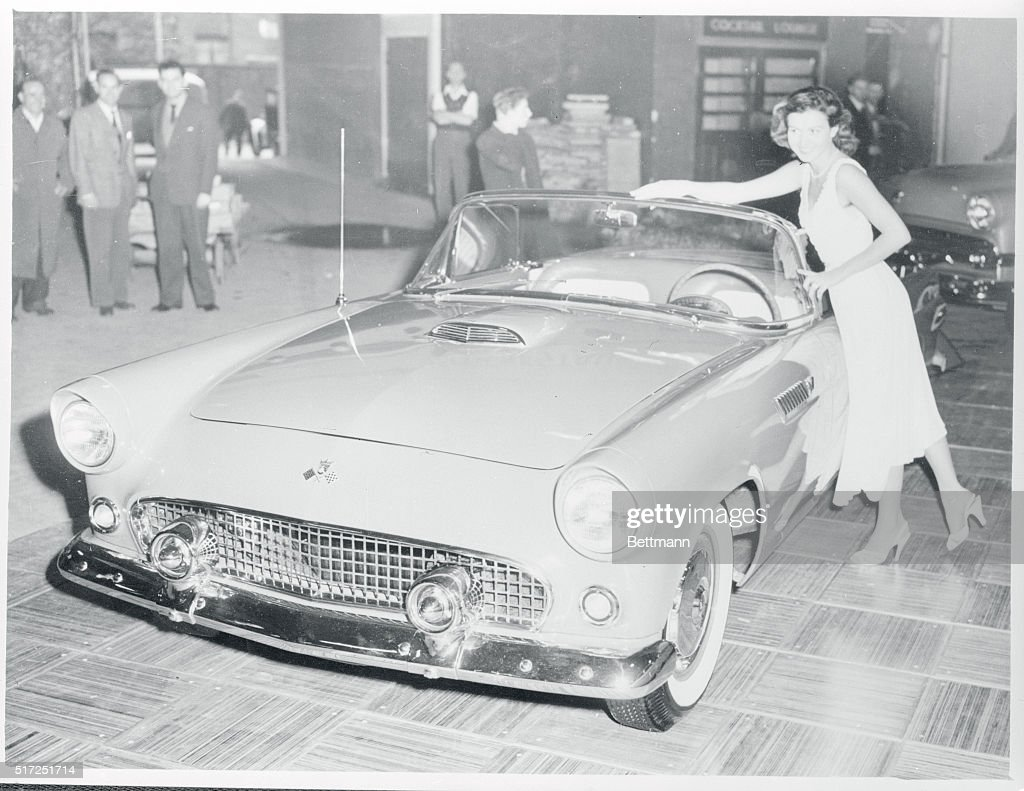 Young Woman Standing Next To Convertible Car
