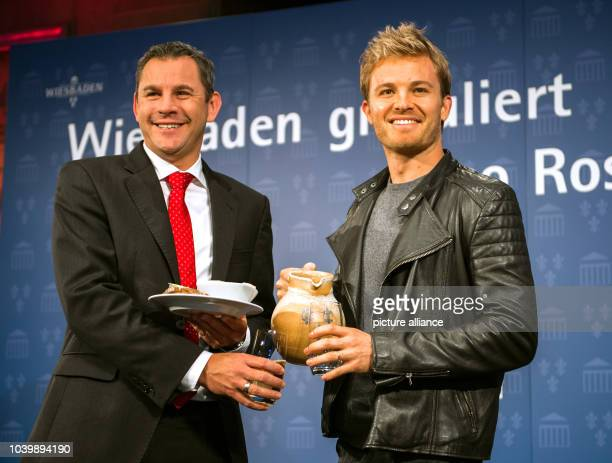 The new Formula 1 world champion Nico Rosberg and mayor Sven Gerich are pictured holding cider and a plate of hand cheese in Wiesbaden Germany 30...