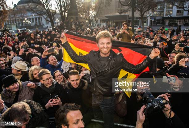 The new Formula 1 world champion Nico Rosberg pictured with a German flag surrounded by fans in Wiesbaden Germany 30 November 2016 Nico Rosberg was...