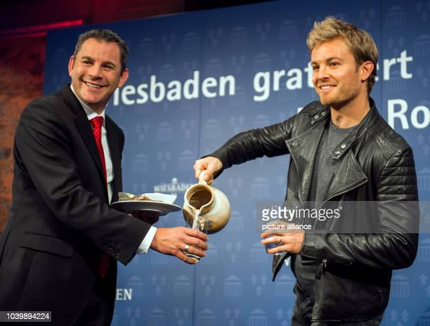 The new Formula 1 world champion Nico Rosberg pours cider for mayor Sven Gerich who is holding a plate of hand cheese in Wiesbaden Germany 30...