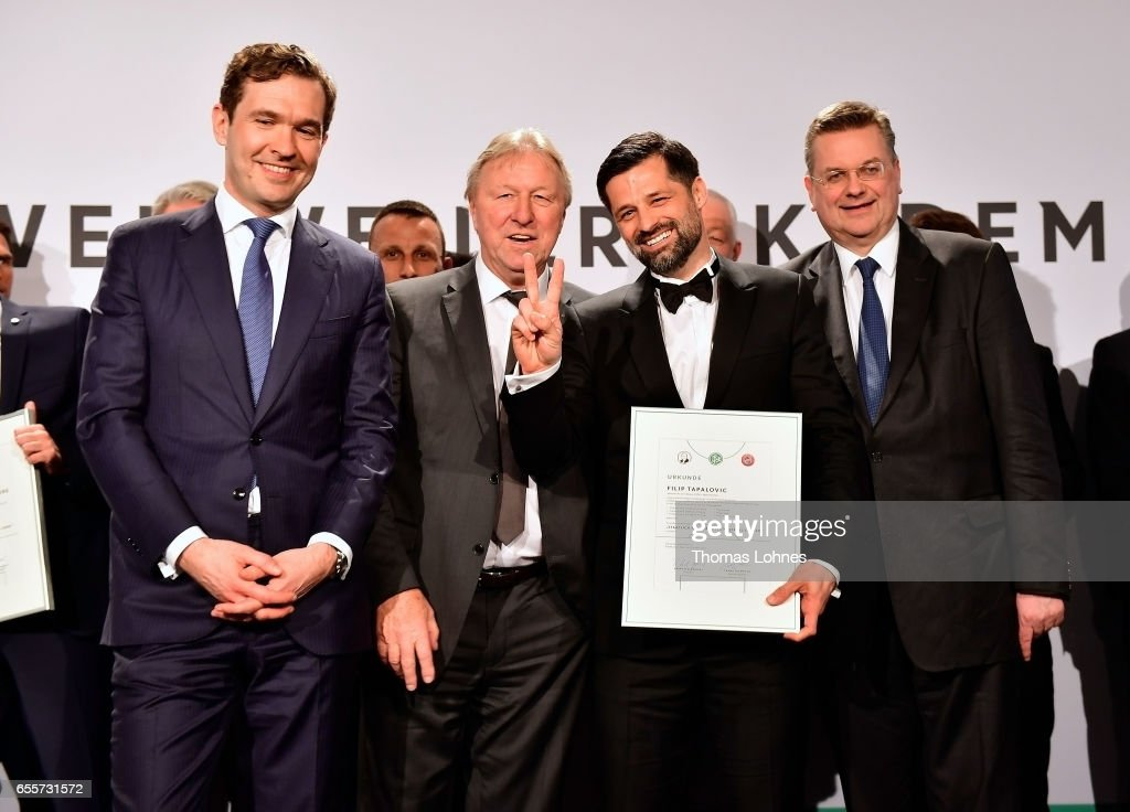 The new fototball coach Filip Tapalovic stands with his certificate between DFB general secretary Friedrich Curtius, Horst Hrubesch and DFB president Reinhard Grindel (L-R) during the 'Coaching Award Ceremony & Closing Event UEFA Pro Coaching Course 2016/2017' on March 20, 2017 in Neu Isenburg, Germany.