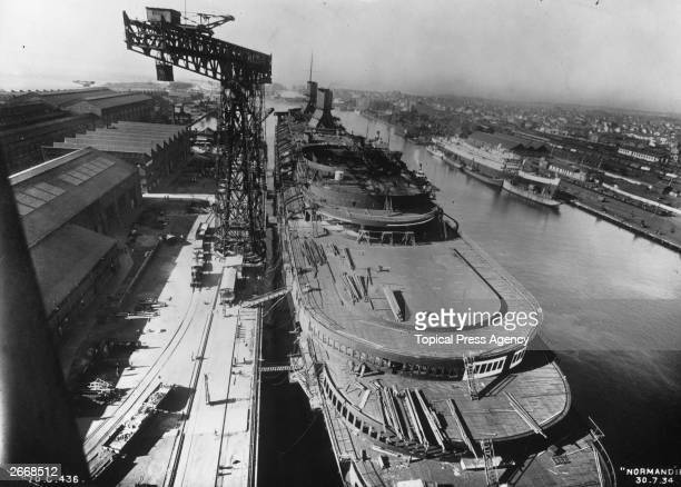 The new French transatlantic liner Normandie the only CGT vessel to win the coveted Blue Riband in her fitting out berth at SaintNazaire Dwarfed by...