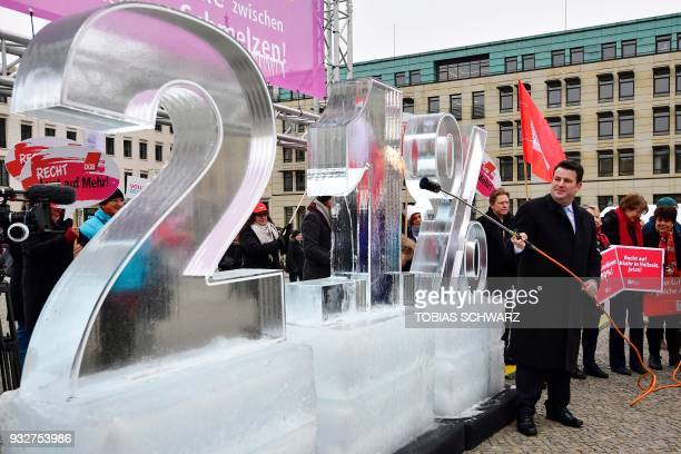 The new German Labour Minister Hubertus Heil melts an ice sculpture featuring '21 percent' to set a sign against the salary gap between female and...