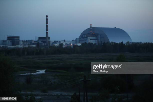 The new giant enclosure that covers devastated reactor number four at the Chernobyl nuclear power plant stands at twilight on August 17 2017 near...