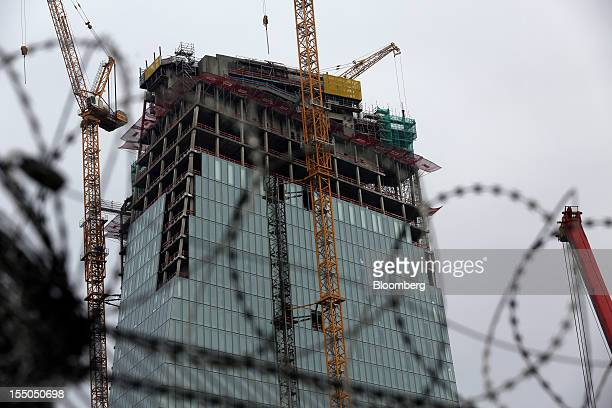 The new headquarters of the European Central Bank still under construction stands beyond a barbedwire fence in Frankfurt Germany on Tuesday Oct 30...