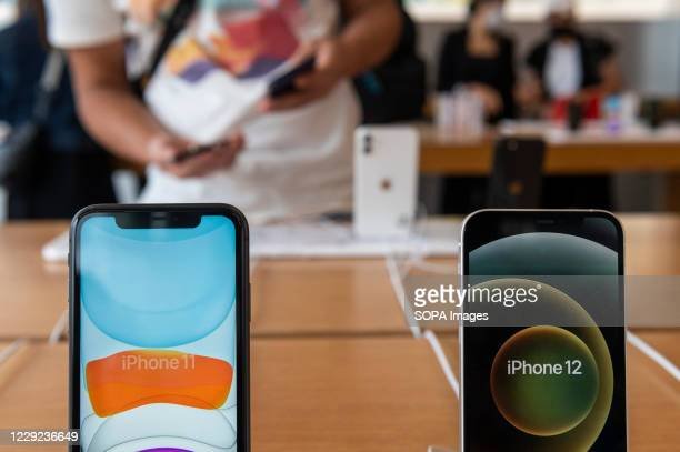 The new iphone 12 smartphone next to the Iphone 11 as a customer tests in the background Apple brand products at an Apple store during the launch day...